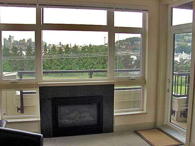Living room, with gas fireplace and picture windows, of 1730 N. Northlake Way, Unit 311. The 1,069-square-foot home, built in 2002, has two bedrooms, two bathrooms and a wrap-around deck with views of Lake Union and downtown. It's listed for $638,000. Photo: Mark Anderson/John L. Scott Real Estate