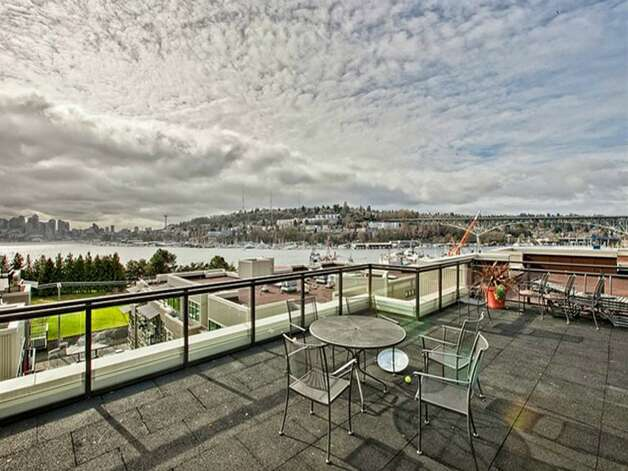 Roof deck of 1730 N. Northlake Way. The 1,069-square-foot home, built in 2002, has two bedrooms, two bathrooms, a gas fireplace, picture windows and a wrap-around deck with views of Lake Union and downtown. It's listed for $638,000. Photo: Mark Anderson/John L. Scott Real Estate