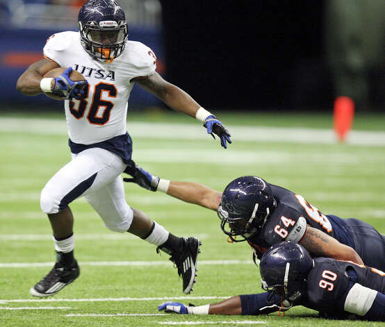 Evans Okotcha (from left) looks for running room around Franky Anaya and Jarron Harris during the 2012 UTSA Football Fiesta Spring Game held Sunday April 15, 2012 at the Alamodome. Photo: EDWARD A. ORNELAS, SAN ANTONIO EXPRESS-NEWS / © SAN ANTONIO EXPRESS-NEWS (NFS)