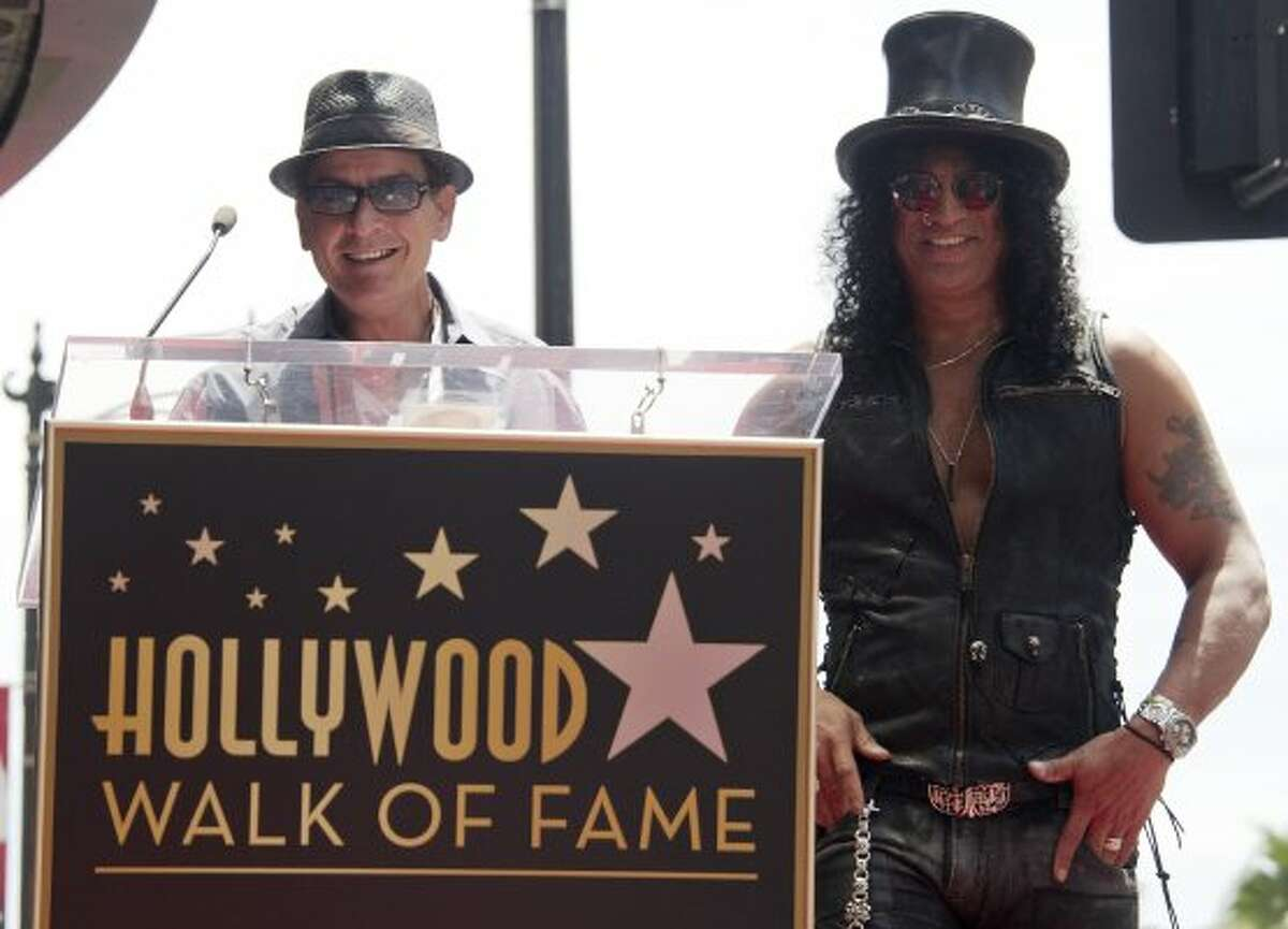 Actor Charlie Sheen (L) speaks as musician and songwriter Slash (R) is a honored with a Star on the Hollywood Walk of Fame on July 10, 2012 in Hollywood, California. (JOE KLAMAR / AFP/Getty Images)