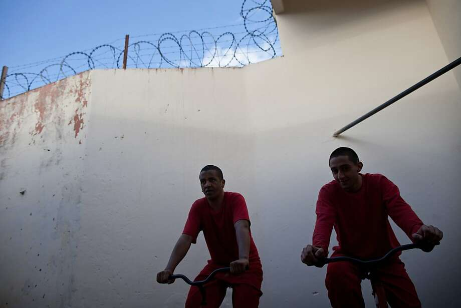 In this Friday, July 6, 2012, inmates pedal stationary bikes to charge car batteries at a prison in Santa Rita do Sapucai, Brazil. An innovative program allows inmates at this medium-security prison to shave days off their sentence in exchange for riding stationary bikes hooked up to converted car batteries that are used to illuminate Santa Rita do Sapucai's town square. (AP Photo/Felipe Dana) Photo: Felipe Dana, Associated Press