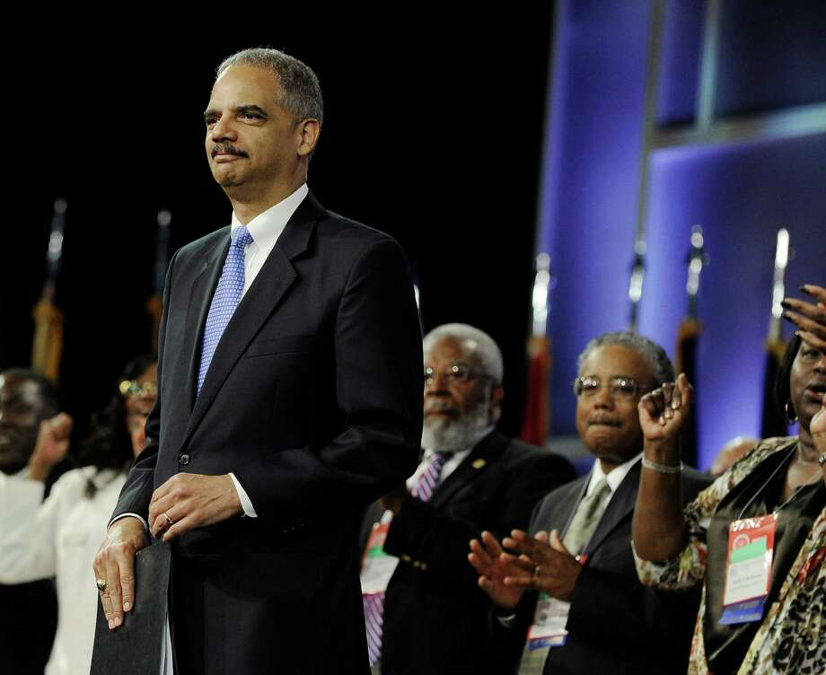 Attorney General Eric Holder is welcomed at the NAACP annual convention Tuesday, July 10, 2012, in Houston. Holder says he opposes a new photo ID requirement in Texas elections because it would be harmful to minority voters. Photo: Pat Sullivan, AP / AP