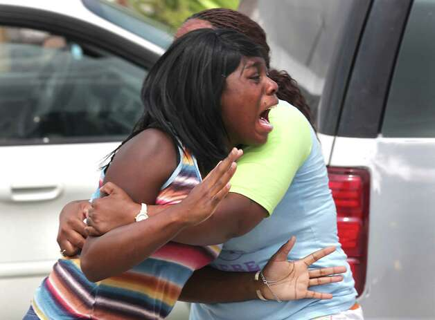 An unidentified woman screams in anguish for her brother, one of the victims of the triple shooting at King's Used Cars, 5380 N. Foster Road, on Tuesday, July 10, 2012. Photo: Bob Owen, San Antonio Express-News / © 2012 San Antonio Express-News
