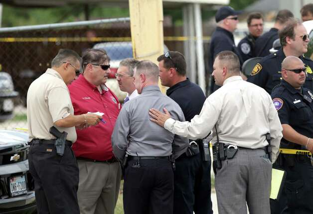 Bexar County sheriff's deputies discuss evidence at the scene of a triple shooting at King's Used Cars, 5380 N. Foster Road, on Tuesday, July 10, 2012. People nearby said they heard shots, then saw two men drive away in a green, four-door sedan. Photo: Bob Owen, San Antonio Express-News / © 2012 San Antonio Express-News
