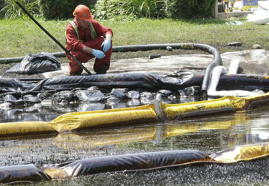 FILE - In this July 29, 2010, file photo, a worker monitors water in Talmadge Creek in Marshall Township, Mich., near the Kalamazoo River as oil from a ruptured pipeline, owned by Enbridge Inc., is attempted to be trapped by booms. Federal investigators are expected to present their findings Tuesday, July 10, 2012 on the likely cause of a pipeline rupture that spilled more than 800,000 gallons of crude oil into the river nearly two years ago. (AP Photo/Paul Sancya, File) Photo: Paul Sancya, Associated Press