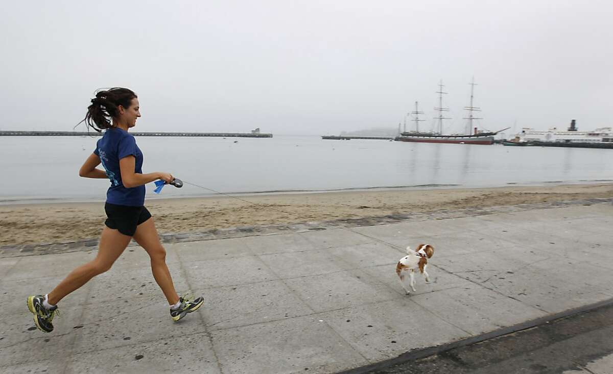 Joanna Reuland trains for the San Francisco Marathon at Aquatic Park with her dog Cooper in San Francisco.