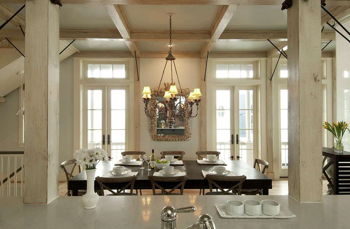 The most formal room in Carol and Mike Linn's Beachtown home is for dining. They brought the chandelier from a previous residence at the Huntington in Houston and found the iron table and the oyster shell mirror with help from Dallas designer Katie Harris.