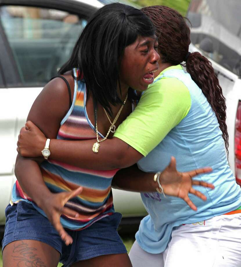 An unidentified woman screams in anguish for her brother, one of the victims of the triple shooting at King's Used Cars, 5380 N. Foster Road. Photo: Bob Owen, San Antonio Express-News / © 2012 San Antonio Express-News
