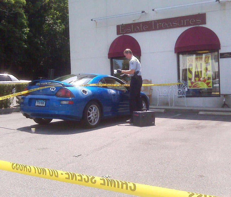 A Greenwich police officer investigates the armed robbery at Estate Treasures in Riverside in July 2009. Photo: File Photo, ST / Greenwich Time File Photo