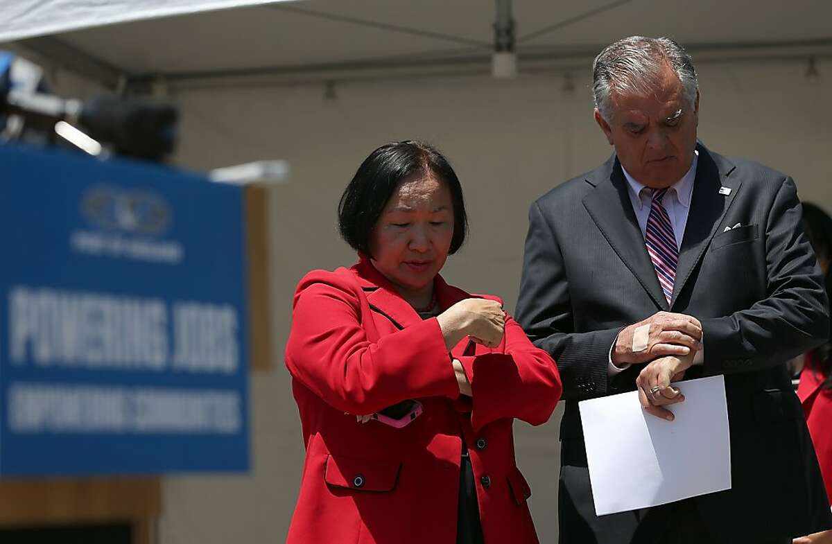 United States Secretary of Transportation Ray LaHood (R) and Oakland Mayor Jean Quan (L(L) check their watches during a news conference at the Port of Oakland on July 9, 2012 in Oakland, California.