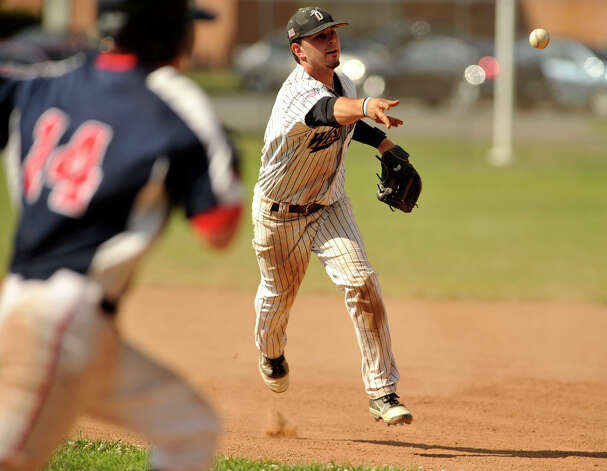 Holyoke's Evan Potter, left, reaches first after Danbury second baseman Josh Ake tosses the ball wide to first base during the Westerners' second game of their double-header against Holyoke at Rogers Park in Danbury on Tuesday, July 10, 2012. Danbury won, 5-2. Photo: Jason Rearick / The News-Times