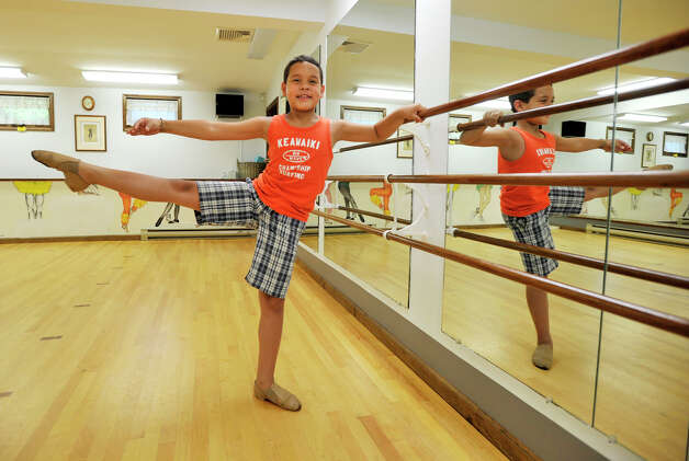 Mckenzie Bernardino, 9, demonstrates a developpe ala seconde, a ballet position, at Academy of Dance Arts in Brookfield on Tuesday, July 10, 2012. Photo: Jason Rearick / The News-Times