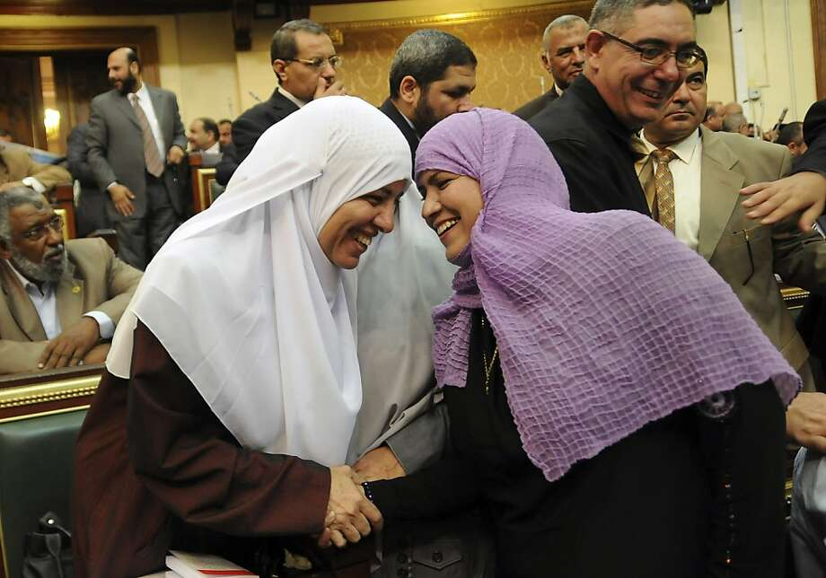 Two female Egyptian lawmakers greet each other at a brief session of Parliament, the first since the country's high court ruled the chamber unconstitutional, in Cairo, Egypt, Tuesday, July 10, 2012. Egypt's Islamist-dominated parliament convened Tuesday in defiance of a ruling by the country's highest court and swiftly voted to seek a legal opinion on the decision that invalidated the chamber over apparent election irregularities. (AP Photo/Mohammed Asad) Photo: Mohammed Asad, Associated Press