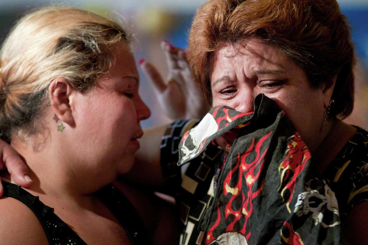 Laura Garcia, left, and Calixta Lara, sister of shooting victim Rufino Lara, embrace at a news conference Tuesday in Houston where the Greater Houston Coalition for Justice and the Lara family disputed the official version of events.