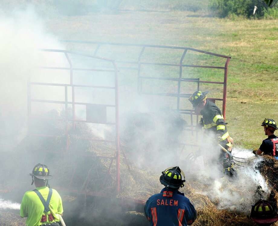 Firefighters from numerous companies in Washington and Saratoga Counties work to knock down a stubborn fire in hay trailers at 229 Spraguetown Road in Greenwich, N.Y. July 10, 2012. Four wagons full of hay and one tractor were damaged in the blaze according to fire officials on the scene.  (Skip Dickstein / Times Union) Photo: SKIP DICKSTEIN