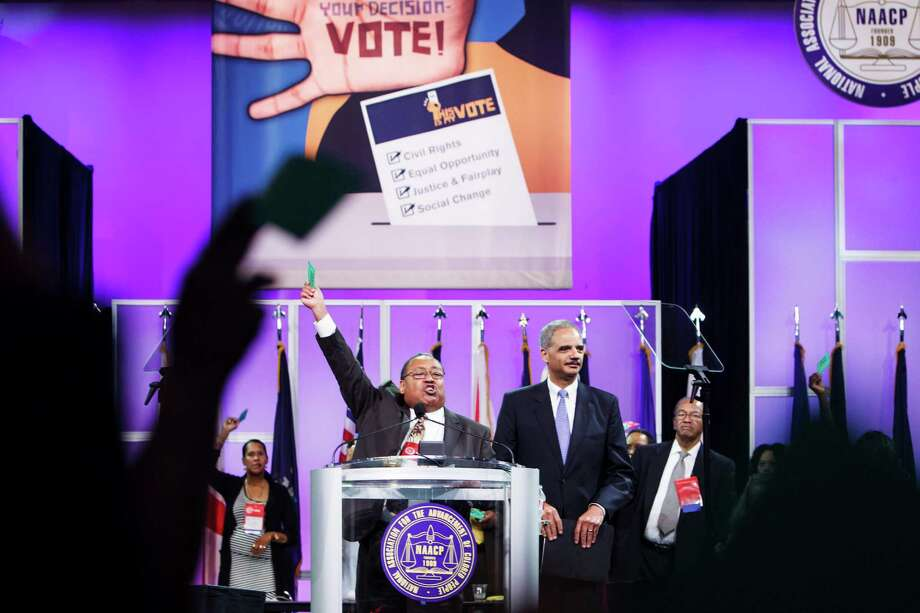 With U.S. Attorney General Eric Holder at his side, NAACP Board Vice Chairman Leon Russell, center, holds up a voting card Tuesday and calls for a resolution at the NAACP convention in support of the embattled administration official. Photo: Michael Paulsen / © 2012 Houston Chronicle