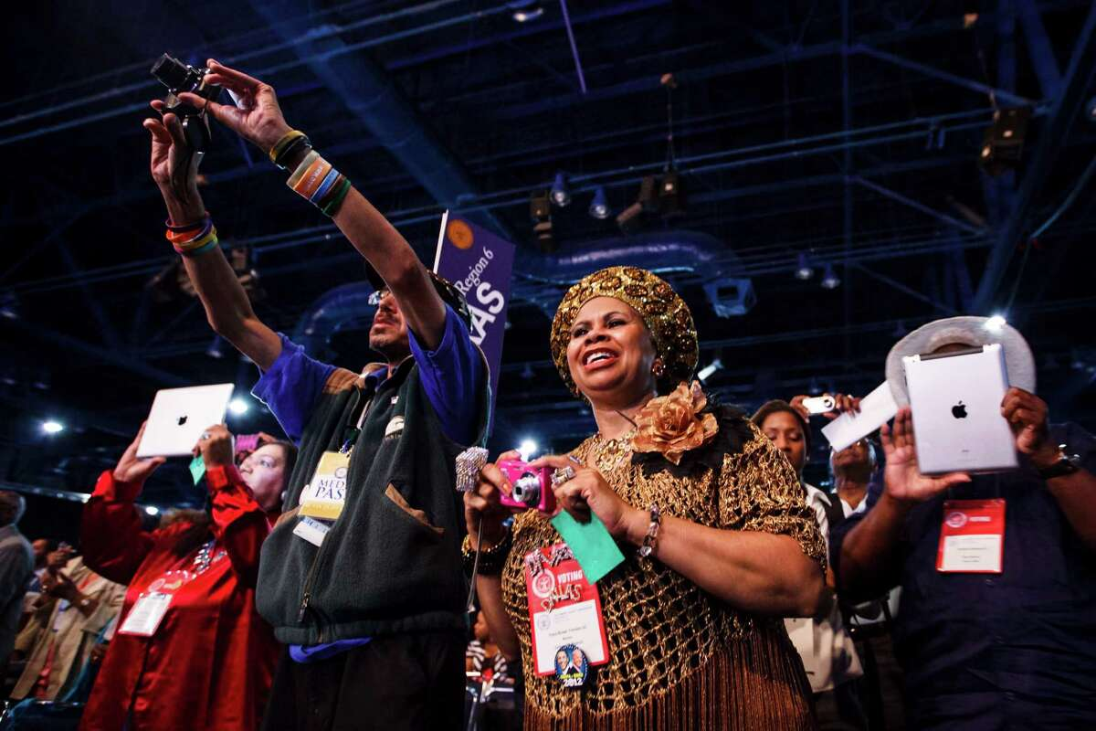 """Clara Brown Trimble, center, and others snap picture as Attorney General Eric Holder speaks at the NAACP National Convention at the George R. Brown Convention Center on Tuesday. Holder, held in contempt of Congress during the investigation of the """"Fast and Furious"""" gun-running operation, got a standing ovation."""