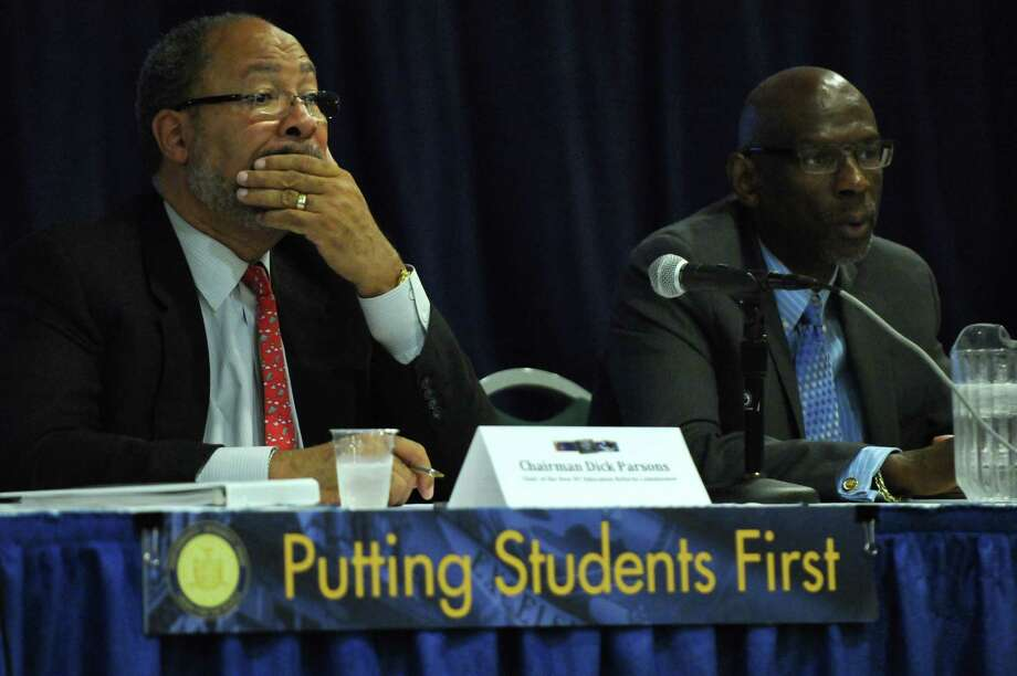 Dick Parsons, Chair of the New NY Education Reform Commission, left, and Geoffrey Canada, Founder and CEO of Harlem Children's Zone, right,  listen to a speaker as he gives input about the state's public education system,  during a public hearing at the Empire State Plaza on Tuesday  July 10, 2012 in Albany, NY.  (Philip Kamrass / Times Union) Photo: Philip Kamrass / 00018392A