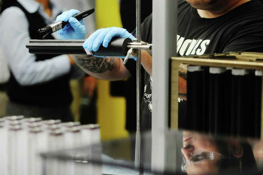 GE employee Nick Esposito applies a carbon paint to the outside of the ceramic tubes that will be used in the company's durathon battery  at GE's new battery plant on Tuesday, July 10, 2012 at the GE campus in Schenectady, NY.   (Paul Buckowski / Times Union) Photo: Paul Buckowski