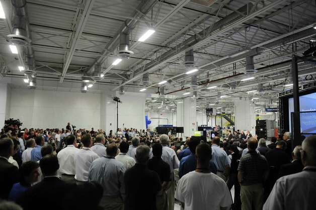 GE employees along with visitors listen as Brandon Harcus, far background at podium, a division manager for Megatron Federal Telecommunications, addresses them at the opening of the company's new battery plant on Tuesday, July 10, 2012 at the GE campus in Schenectady, NY.  The plant will use GE's durathon battery technology in manufacturing  batteries for customers like Megatron Federal Telecommunications. (Paul Buckowski / Times Union) Photo: Paul Buckowski