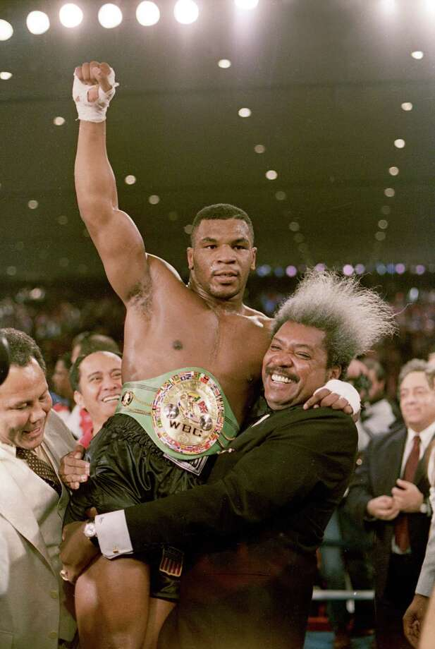 ** FILE ** Boxing promoter Don King lifts new heavyweight champion Mike Tyson atfer Tyson beat Trevor Berbick in a second round TKO in Las Vegas, Nev., on Nov. 22, 1986.  Tyson burned through ring earnings totalling in the hundreds of millions of dollars and now has his hopes for financial resurrection pegged on a lawsuit claiming  King swindled him of out of millions. (AP Photo/Doug Pizac) Photo: DOUG PIZAC / AP