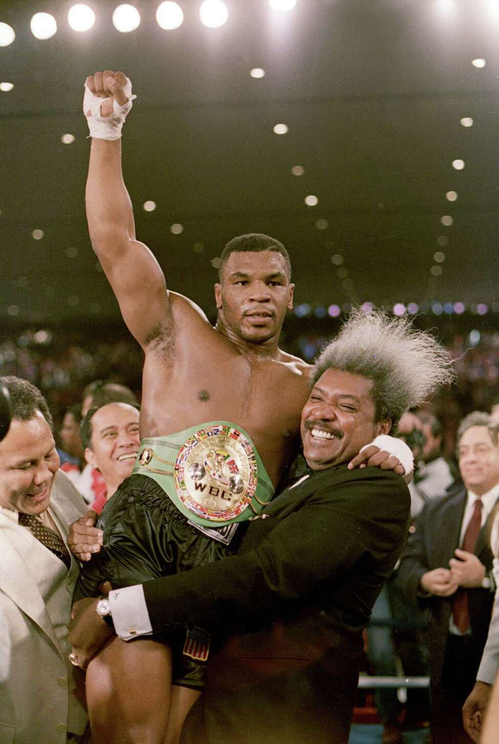 ** FILE ** Boxing promoter Don King lifts new heavyweight champion Mike Tyson atfer Tyson beat Trevor Berbick in a second round TKO in Las Vegas, Nev., on Nov. 22, 1986. Tyson burned through ring earnings totalling in the hundreds of millions of dollars and now has his hopes for financial resurrection pegged on a lawsuit claiming King swindled him of out of millions. (AP Photo/Doug Pizac)