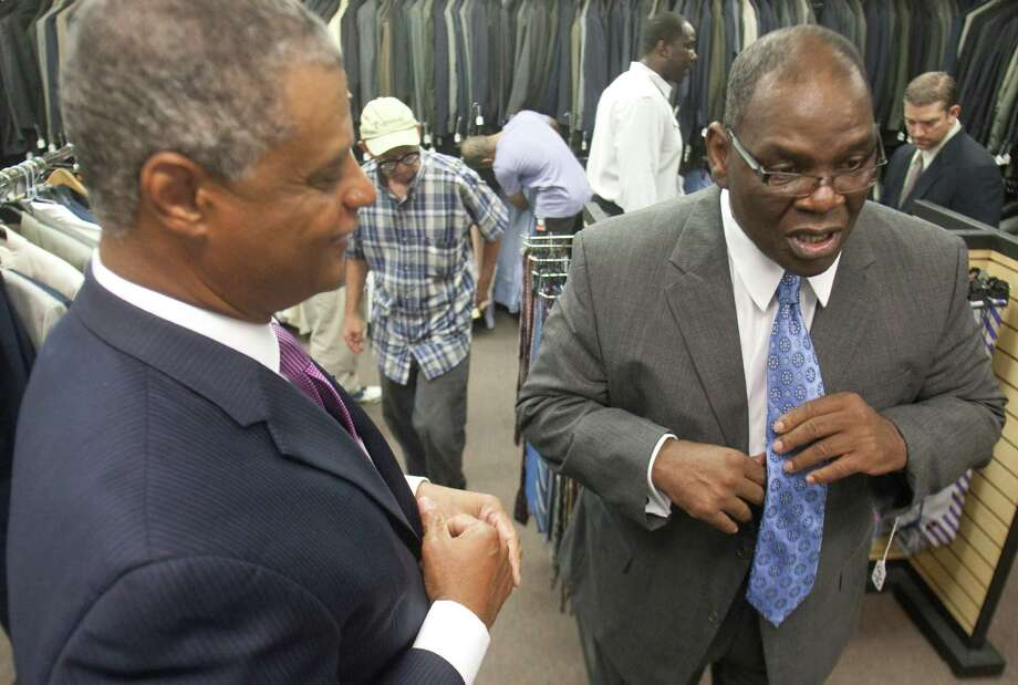 Steve Cook, left, of Men's Wearhouse helps James Williams select a tie at Career Gear, which provides free suits to men who need them for job interviews. Cook is vice president of community relations and corporate giving for Men's Wearhouse. Photo: J. Patric Schneider / Houston Chronicle