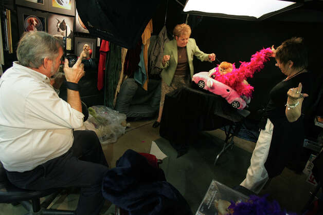 Mimi, a Pomeranian, gets the royal treatment while being photographed by professionals Tom and Sande Weigand and her handler Valerie Humbird (second from left) at the River City Cluster of Dog Shows on July 26, 2006 at the Convention Center. Photo: Kin Man Hui, San Antonio Express-News / © San Antonio Express-News
