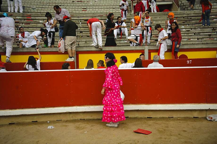 A man wearing a typical Spanish female dress looks on after jumping to the arena at the end of a bullfight of the San Fermin festival, in Pamplona, Spain, Tuesday, July 10, 2012.(AP Photo/Daniel Ochoa de Olza) Photo: Daniel Ochoa De Olza, Associated Press