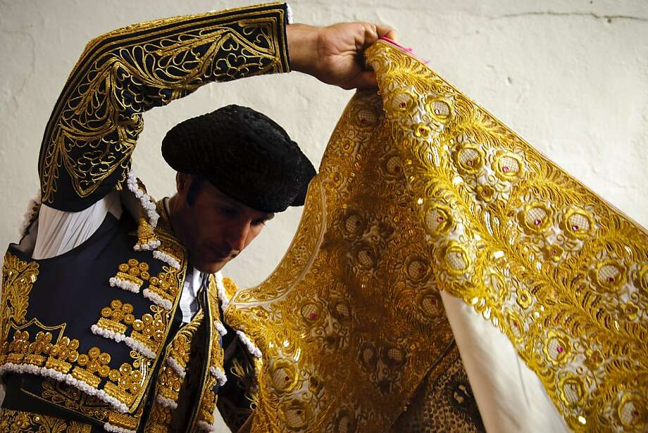 Spanish bullfighter David Mora adjusts his 'capote' before a bullfight of the San Fermin festival, in Pamplona, Spain, Tuesday, July 10, 2012.(AP Photo/Daniel Ochoa de Olza) Photo: Daniel Ochoa De Olza, Associated Press