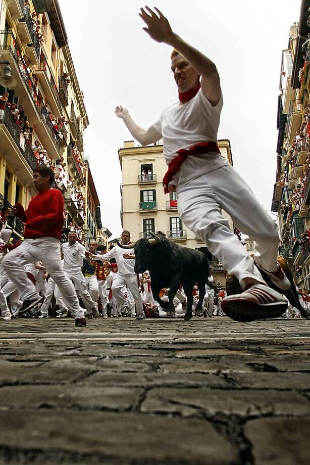 Revelers run in front of a pack of six El Pilar's ranch fighting bulls during the running of the bulls of the San Fermin festival, in Pamplona, Spain, Tuesday, July 10, 2012. (AP Photo/Daniel Ochoa de Olza) Photo: Daniel Ochoa De Olza, Associated Press
