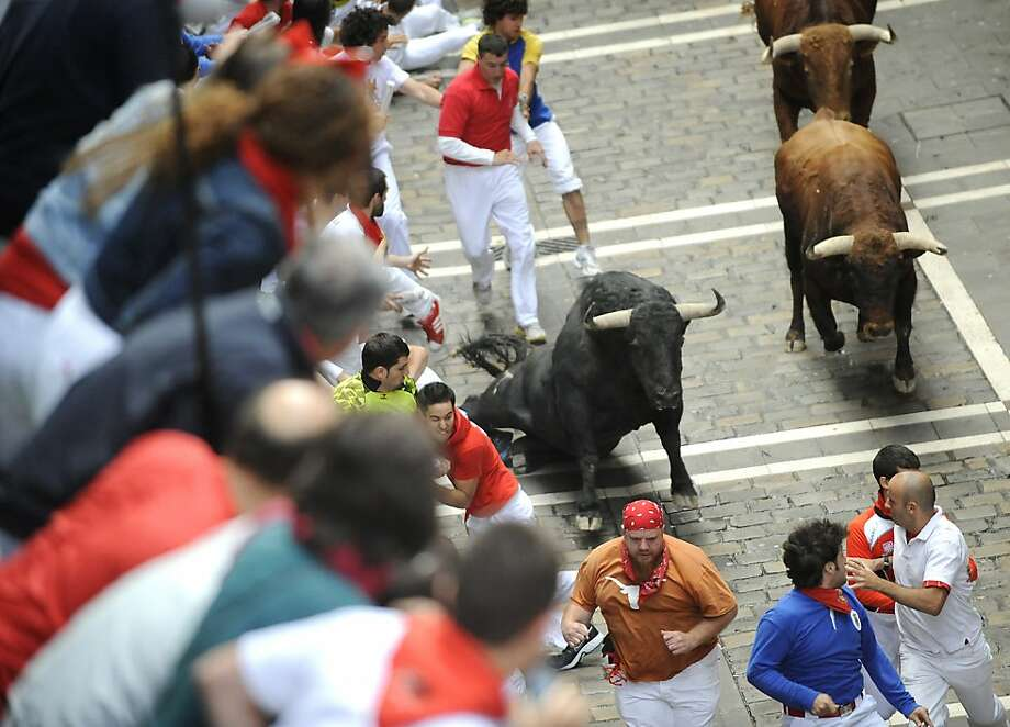Participants run in front of El Pilar's bulls during the fourth San Fermin Festival bull run, on July 10, 2012, in Pamplona, northern Spain. The festival is a symbol of Spanish culture that attracts thousands of tourists to watch the bull runs despite heavy condemnation from animal rights groups. AFP PHOTO / ANDER GILLENEAANDER GILLENEA/AFP/GettyImages Photo: Ander Gillenea, AFP/Getty Images