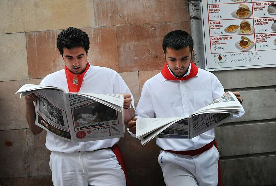 PAMPLONA, SPAIN - JULY 10:  Revelers read a paper as they wait before running with El Pilar fighting bulls along la cuesta de Santo Domingo on the fourth day of the San Fermin running-of-the-bulls on July 10, 2012 in Pamplona, Spain. Pamplona's famous Fiesta de San Fermin, which involves the running of the bulls through the historic heart of Pamplona for eight days starting July 7th, was made famous by the 1926 novel of U.S. writer Ernest Hemmingway called 'The Sun Also Rises.'  (Photo by Jasper Juinen/Getty Images) Photo: Jasper Juinen, Getty Images