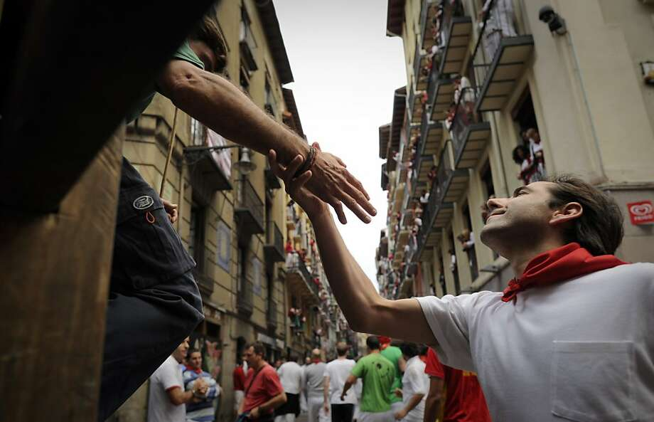 A runner greets a shepherd of Encierro before the fourth run of the bulls of the San Fermin festival, on July 10, 2012, in the Northern Spanish city of Pamplona. The festival is a symbol of Spanish culture that attracts thousands of tourists to watch the bull runs despite heavy condemnation from animal rights groups . AFP PHOTO/Pedro ARMESTREPEDRO ARMESTRE/AFP/GettyImages Photo: Pedro Armestre, AFP/Getty Images