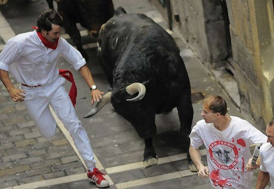 Revelers run on Estafeta street beside to one El Pilar fighting bulls ranch, during the fourth running of the bulls at the San Fermin fiestas, in Pamplona northern Spain, Tuesday, July 10, 2012. (AP Photo/Alvaro Barrientos) Photo: Alvaro Barrientos, Associated Press