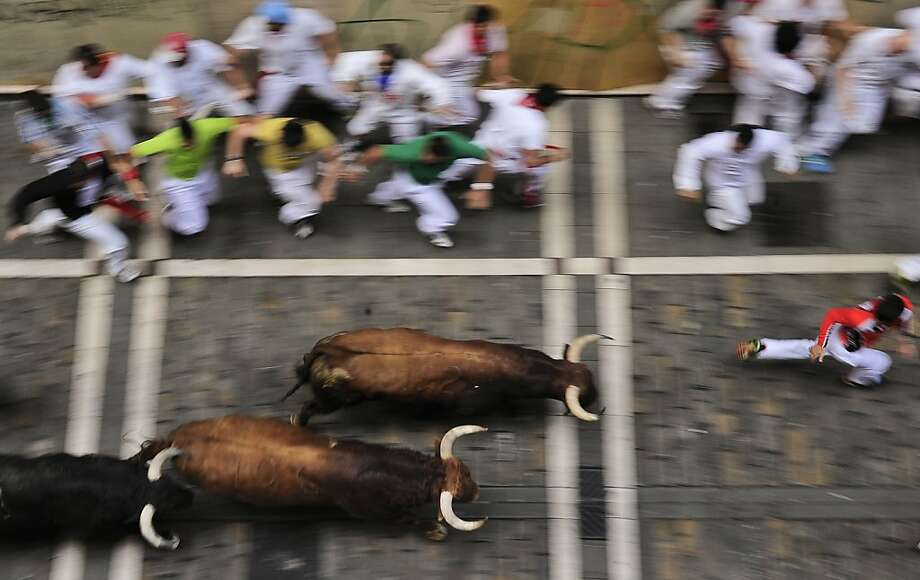 Revelers run on Estafeta street beside to El Pilar fighting bulls ranch, during the fourth running of the bulls at the San Fermin fiestas, in Pamplona northern Spain, Tuesday, July 10, 2012. (AP Photo/Alvaro Barrientos) Photo: Alvaro Barrientos, Associated Press