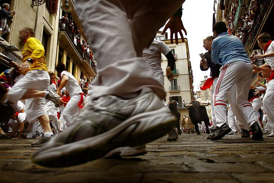 Revelers run in front of a pack of six El Pilar's ranch fighting bulls during the running of the bulls of the San Fermin festival, in Pamplona, Spain, Tuesday, July 10, 2012.(AP Photo/Daniel Ochoa de Olza) Photo: Daniel Ochoa De Olza, Associated Press