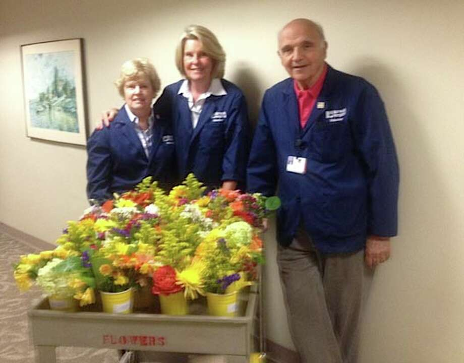 Norwalk Hospital volunteer LaVonne Kramer of Westport, center, is joined by Norwalk residents Nancy Lione and her husband, Fred Lione,also Nowalk Hospital volunteers. They participate in the Flowers for Patients program at the hospital. July 13, 2012, New Canaan, Conn. Photo: Contributed Photo