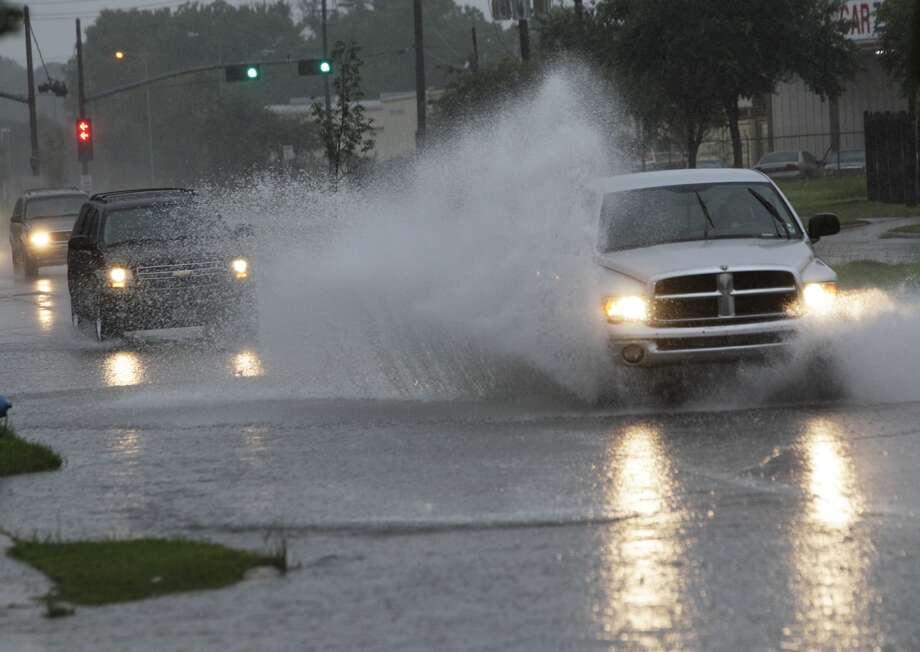 Motorists pass through rain-covered roads along Veterans Memorial at N. Shepherd near Interstate 45 on Wednesday morning. Photo: Melissa Phillip, Houston Chronicle