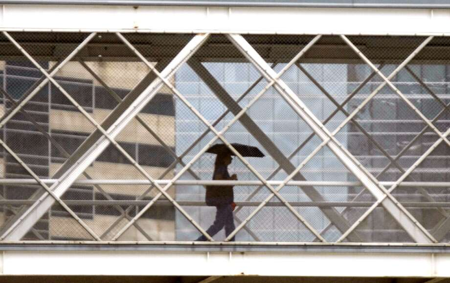 A pedestrian walks across the TMC Transit Center skywalk as rain fell on Houston on Wednesday, July 11, 2012. Photo: Johnny Hanson, Houston Chronicle