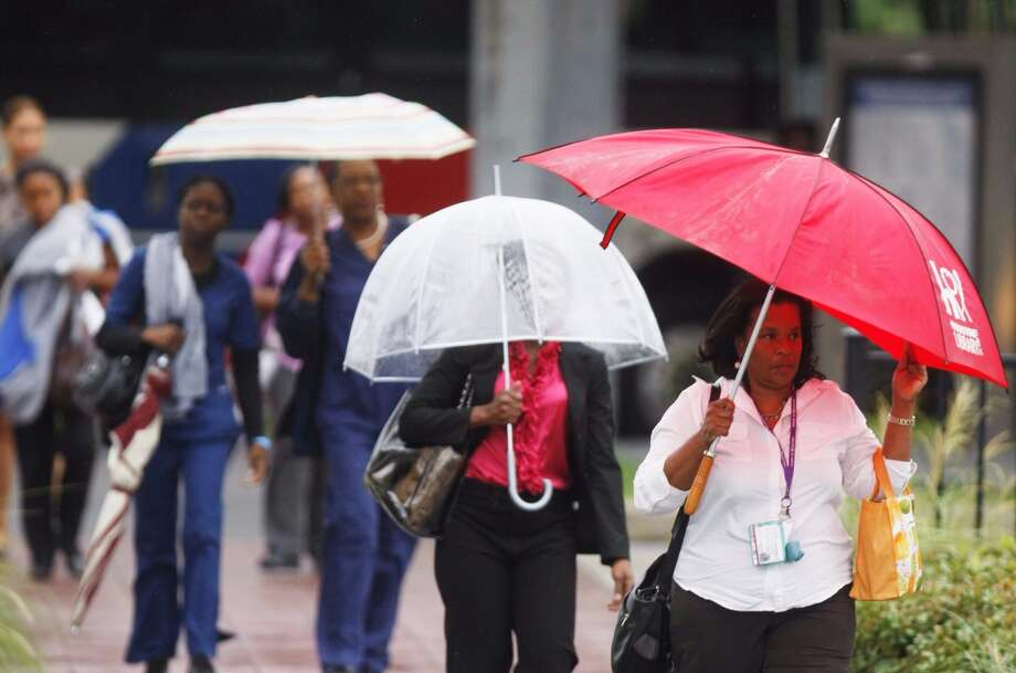 Pedestrians walk through the rain at the TMC Transit Center on the corner of Pressler and Fannin on Wednesday, July 11, 2012. Photo: Johnny Hanson, Houston