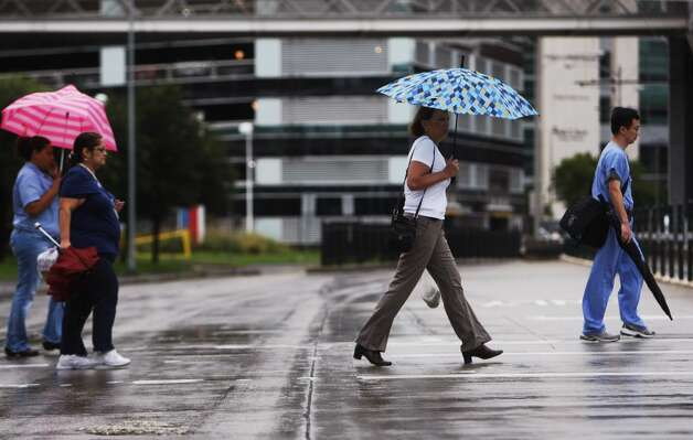 Pedestrians walk through the rain in the Texas Medical Center on the corner of Pressler and Fannin on Wednesday, July 12, 2012. Photo: Johnny Hanson, Houston Chronicle