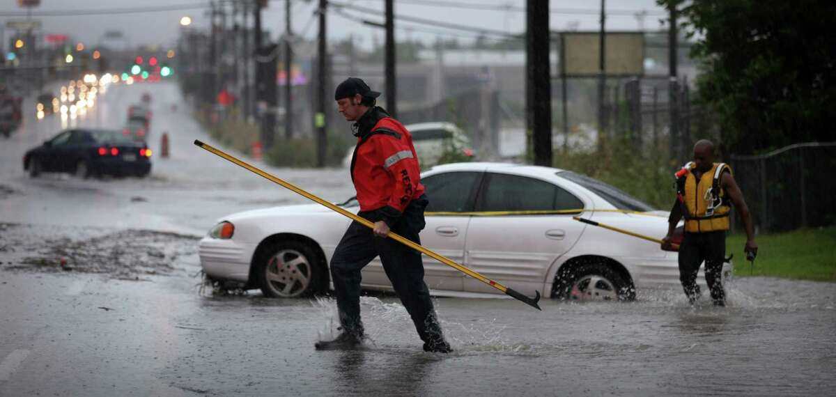 Fire fighters secure a stalled vehicle in high water in the 3500 block of Fredericksburg Rd. Wednesday, July 11, 2012.