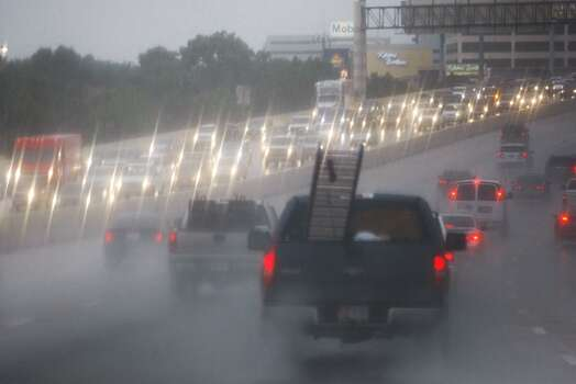 Motorists drive through the rain on the South Loop on Wednesday, July 12, 2012. Photo: Johnny Hanson, Houston Chronicle