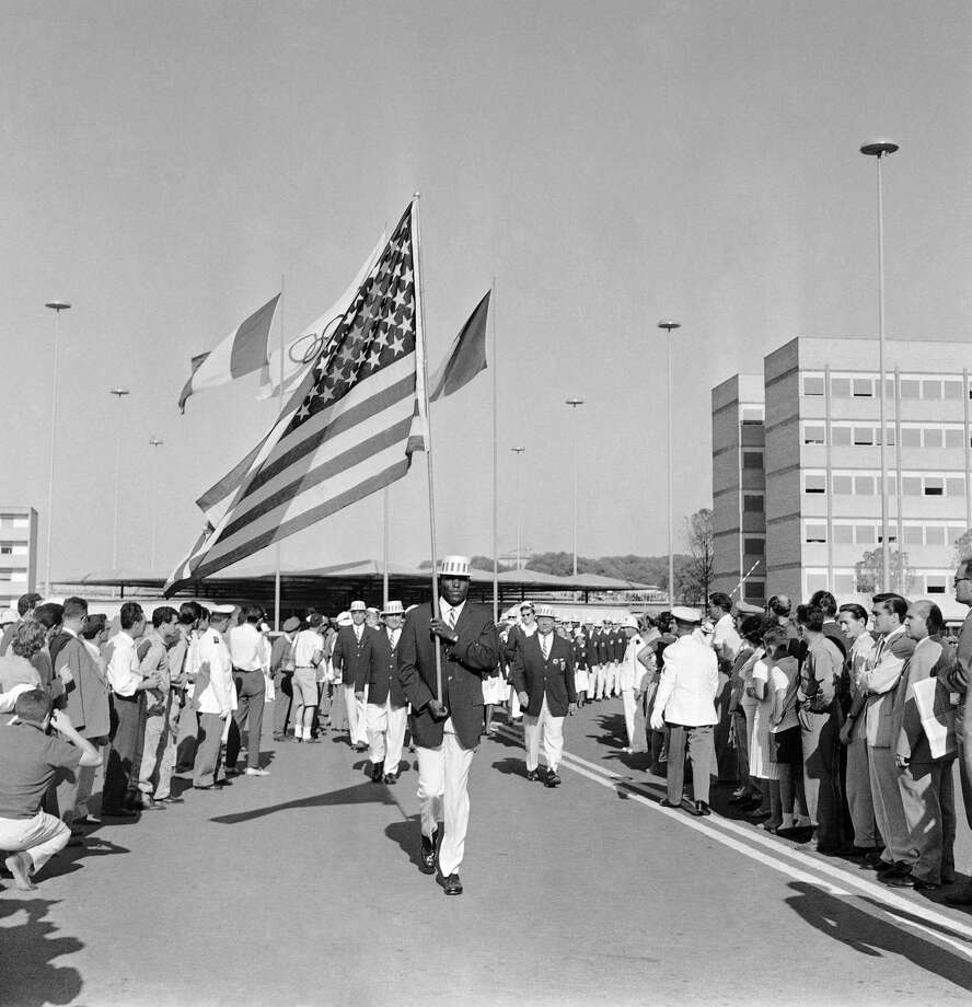 U.S. Flag bearer Rafer Johnson, from  Kingsburt, Calif,  carrying the United States flag as he leads Stars and Stripes the U.S. Olympic team out of the Olympic Village, to march  to the Olympic Stadium for the opening ceremony of the Rome Summer Olympics, August 25, 1960.    Rafer Johnson, world record holder in the Decathlon, and now a member of the U.S. track and field Olympic team, was the first black ever to be named to carry the American flag. Photo: Jim Pringle, AP / 1960 AP