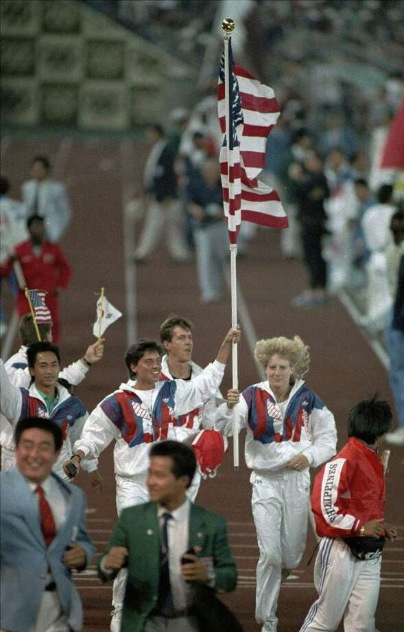 Members of the U.S. Olympic team carry the American flag as they run into the Olympic stadium of Seoul for the closing ceremony of the XXIV Olympiad Sunday night, Oct. 2, 1988. Photo: LIONEL CIRONNEAU, AP / 1988 AP