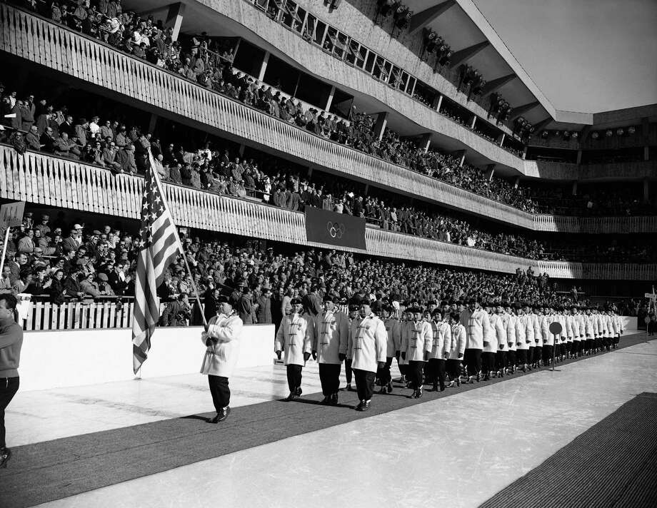 Jim Bickford, 43-year-old bobsledder,  carries U.S. flag as he leads teammates past stands at stadium at Cortina D'Ampezzo during opening ceremonies for 1956 Winter Olympic Games, Jan. 26, 1956, Cortina D'Ampezzo, Italy.  Photo: AP / 1956 AP