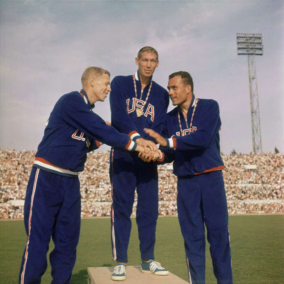Triple handshake between the three winners of the men's 400-meter hurdles race of the Rome Summer Olympics stand on the podium September 5, 1960 for the medal ceremony at the Olympic Stadium.  They are: Glenn Davis; center, winning gold medal; Clifton Cushman, Ill., left, winner of silver medal; and Richard Howard, right, who won the bronze medal. Photo: Anonymous, AP / 1960 AP