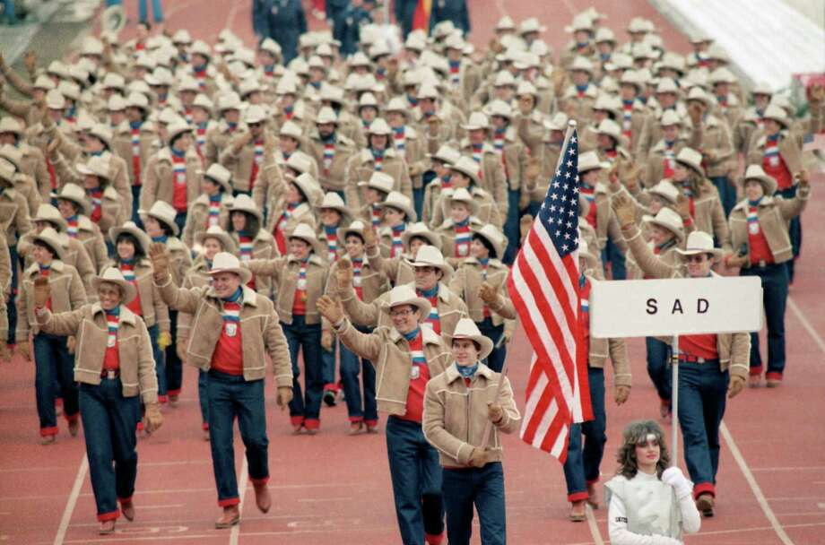 Members of the U.S. Olympic team wave to audience as they march in opening ceremony at Kosevo Stadium in Sarajevo, on Feb. 8, 1984 for the XIV winter Olympic Games. Frank Masley of Newark carries the flag. Placard marked sad is the Yugoslav designation for USA. Photo: Jack Smith, AP / 1984 AP