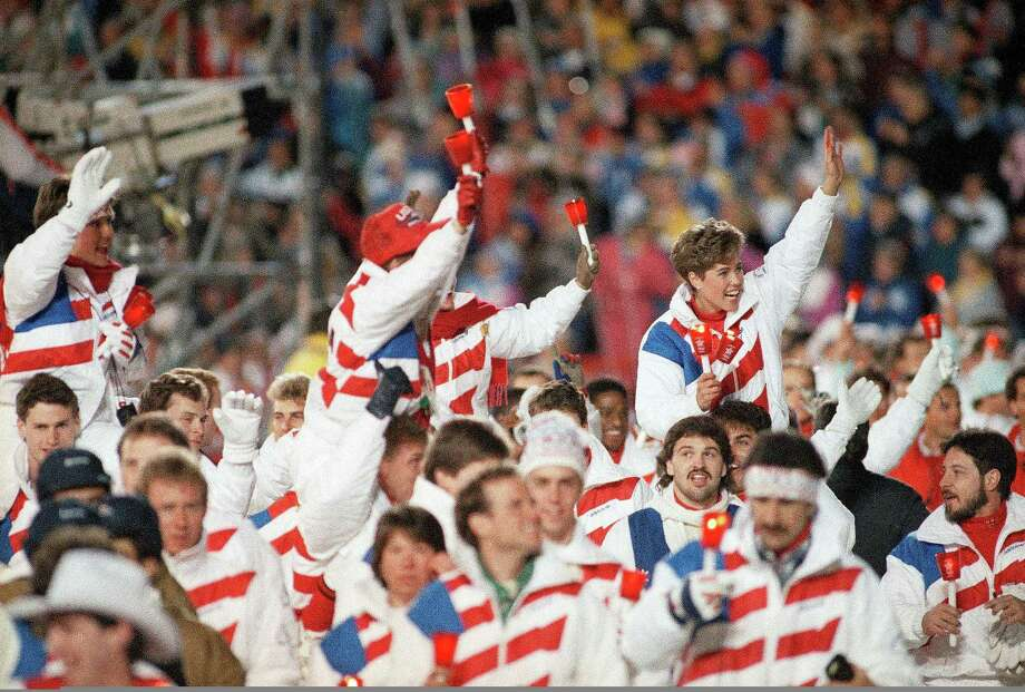 Jill Trenary of Colorado Springs, Colo., is carried on the shoulders of her teammates as the American Winter Olympic team walks into Calgary's McMahon Stadium for the closing ceremony at night on Sunday, Feb. 28, 1988. Photo: Anonymous, AP / 1988 AP